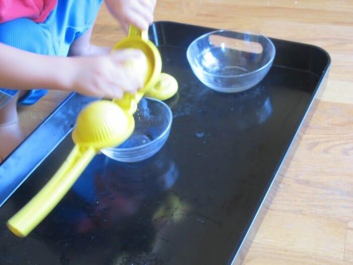 A child squeezing a lemon