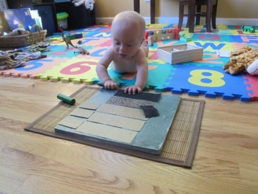 A child exploring a DIY texture board