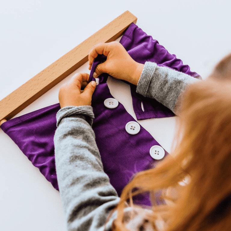 A girl using a Montessori button frame