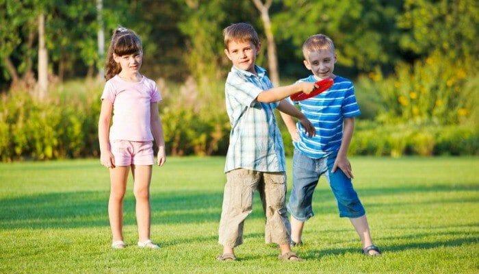 Preschool boy throwing frisbie, his friends looking beside