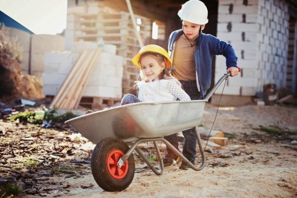 young boy and girl playing on construction site
