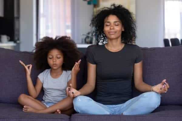 A mom and daughter meditating together.