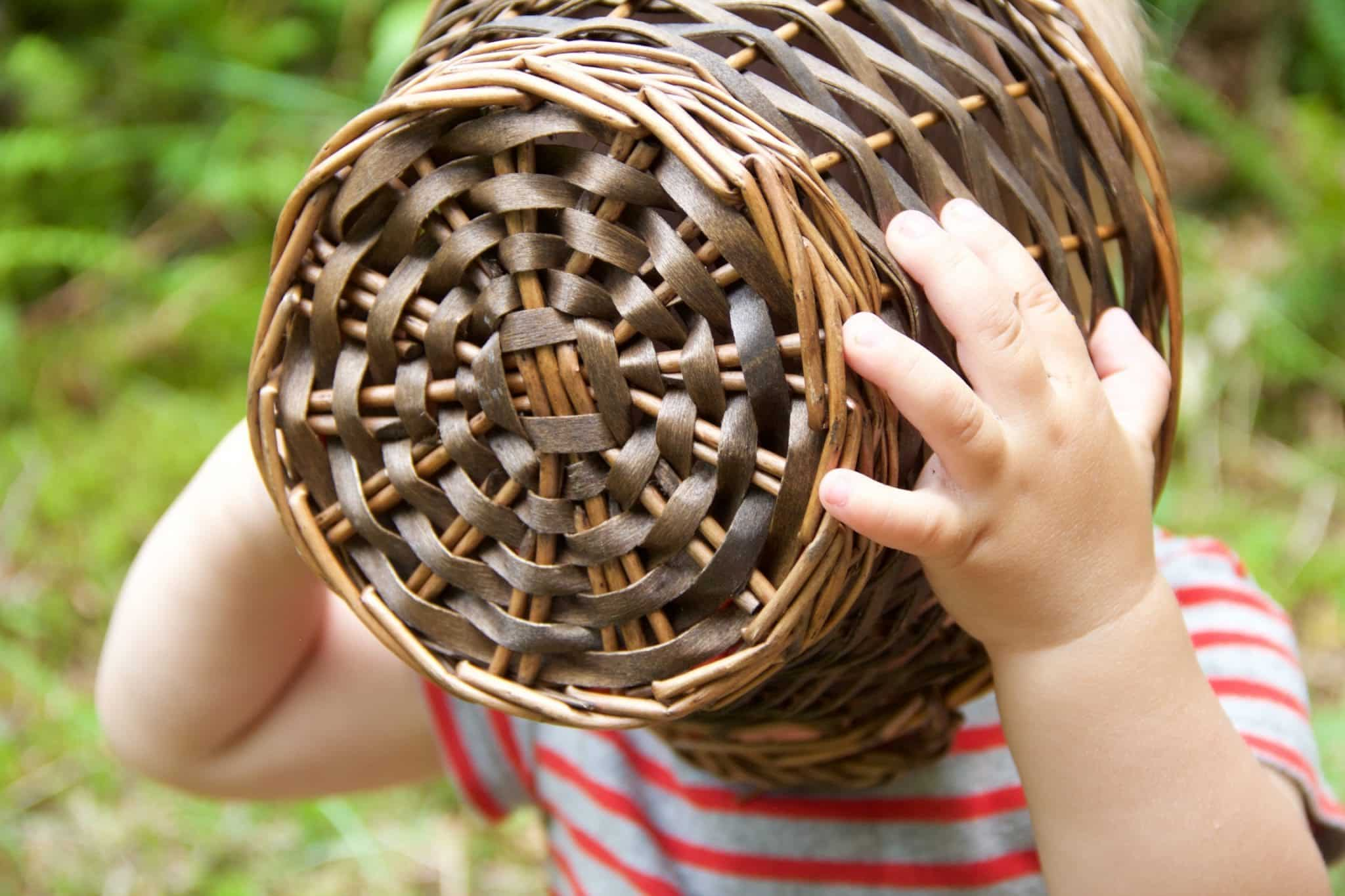 A child with his head in a basket