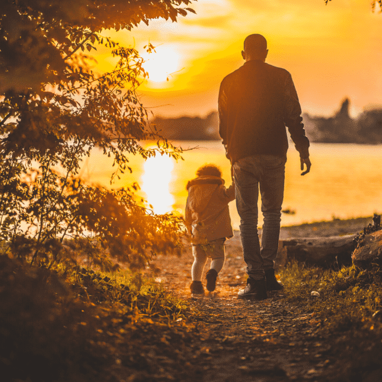 a dad and child holding hands on a walk