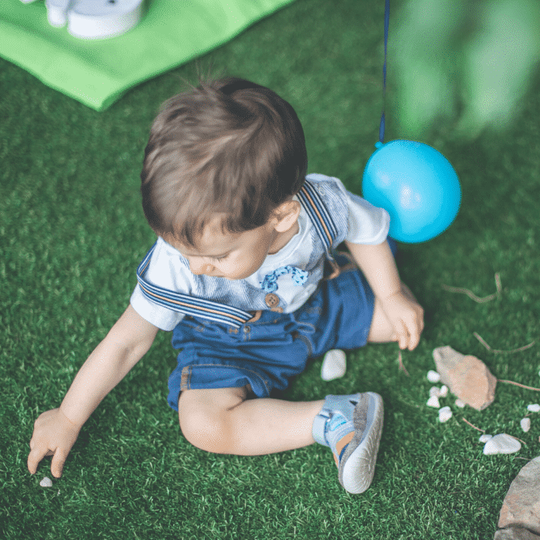one year old boy playing with a rock