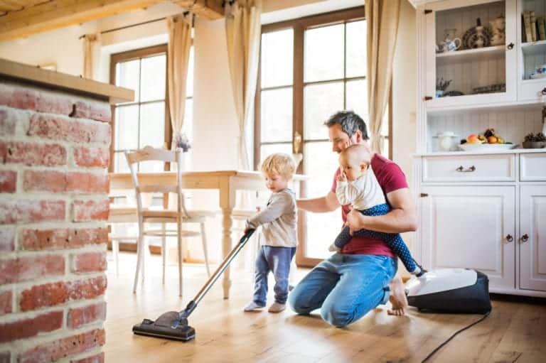 Father and two toddlers doing housework. A child vacuuming.