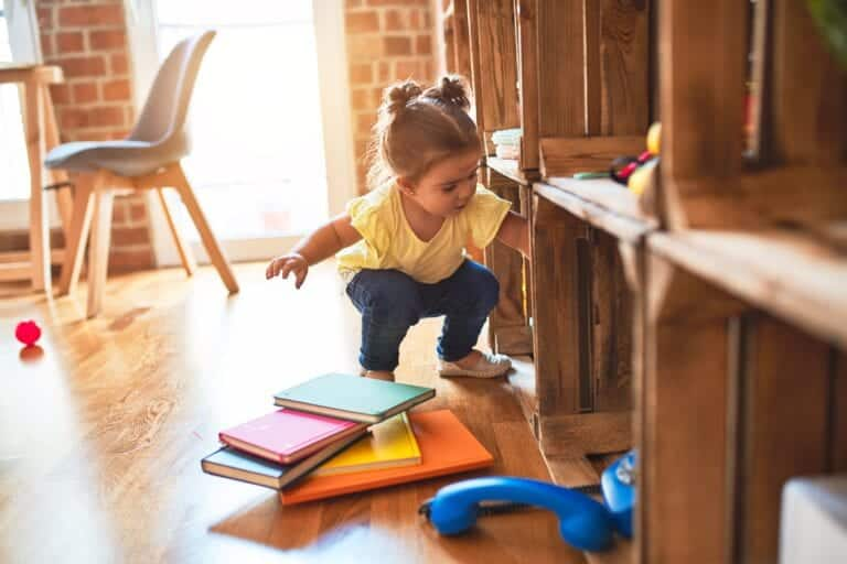Beautiful toddler taking books of shelving at kindergarten