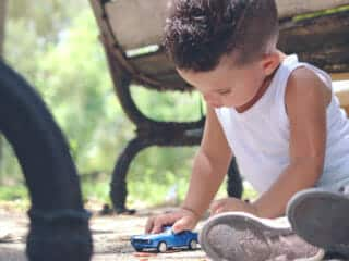 Canva Boy in White Tank Top Playing Blue Coupe Die Cast Near Brown Wooden Bench Chair during Daytime scaled